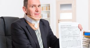Businessman at work wearing neck brace with insirance flaim form in hands